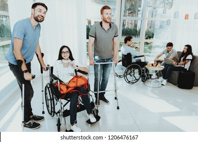People in a Wheelchair. Disabled in the Hall. Woman in a Wheelchair. The man on crutches. Room with panoramic view. Gray sofa. White interior. Meeting Friends with Disabilities. Limited Opportunities.