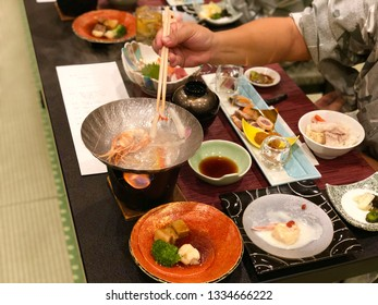 People while used chopsticks take a shrimp and vegetable in small hot pot. Japanese food kaiseki in ryokan.