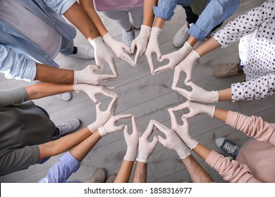 People in white medical gloves showing hearts with fingers indoors, top view