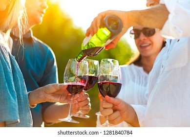 People at wine outdoor party. Wine festival. Man pouring red wine in to the wineglasses
