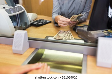 people, withdrawal, saving and finance concept - clerk counting cash money for customer at bank office or currency exchanger