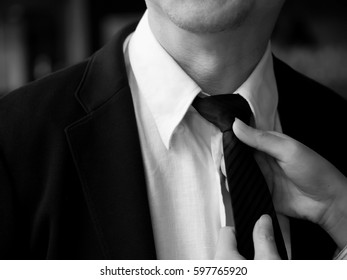 People, Woman helping man and adjusting tie on his neck with soft focus, black and white color tone, business, care and clothing concept