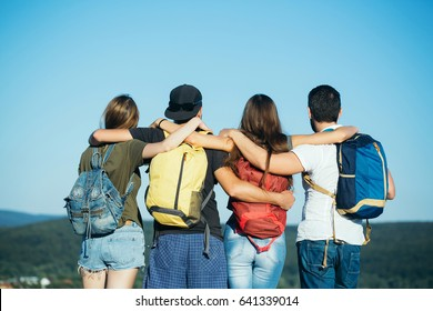 people, women or girls and handsome men watching idyllic landscape on mountain top. Friends or tourists with colorful backpacks on sunny, blue sky. Back view. Summer vacation. Travelling, hiking