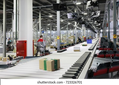 People work in modern workshop with conveyor, many displays in warehouse