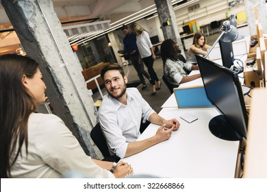 People working at busy modern office in front of computers