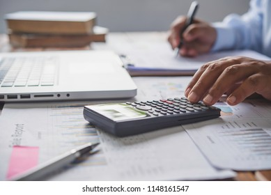 people are working with a calculator and laptop. in office business concept