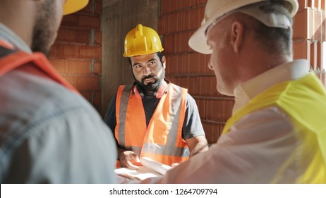 People working in construction site. Men at work in new building. Team of workers at work talking with supervisor and looking at plans