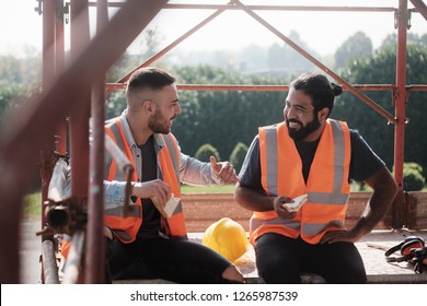 People working in construction site. Men at work in new housing project. Team of happy workers laughing, talking and eating snack during lunch break