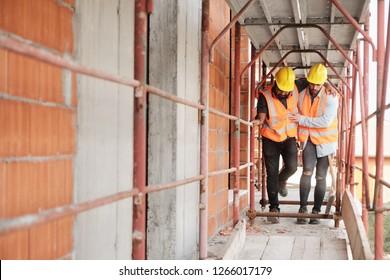 Menschen, die auf Baustellen arbeiten. Junge Männer arbeiten in einem neuen Haus im Wohngebäude. Latino-Handarbeiter, der verletzten Mitarbeitenden nach Arbeitsunfall hilft