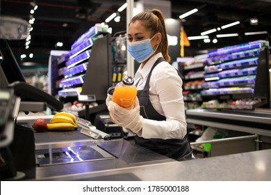 People working during global virus pandemic. Cashier at supermarket wearing mask and gloves fully protected against corona virus.