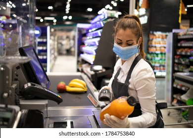 People working during virus pandemic. Cashier in supermarket wearing mask and gloves fully protected against corona virus.