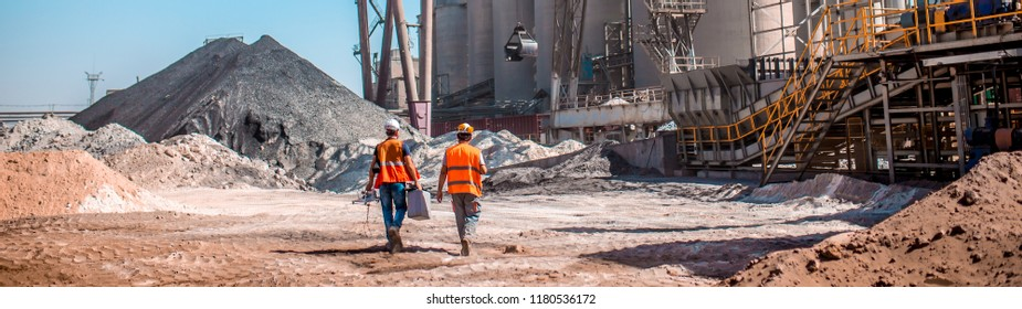 People are working in the industry. Modern technologies work at a cement plant. Technological work on the production of cement. Working atmosphere with copy space. Heaps of sand and soil raw materials