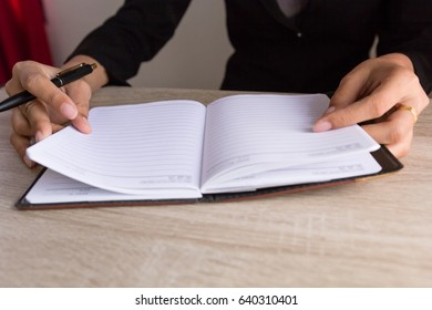 People writing on notebook on wooden table