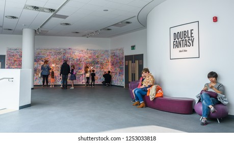 "People writing on the Peace Wall encoutaged by Yoko Ono to ""Add colour where the world needs peace"" at  the ""Double Fantasy"" ehibition in Liverpool museum August 2018."