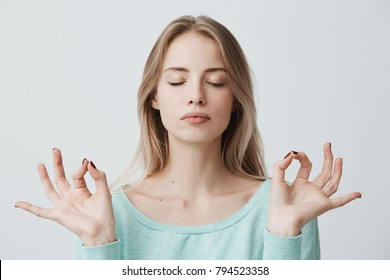 People, yoga and healthy lifestyle. Gorgeous young blonde woman dressed in light blue sweater keeping eyes closed while meditating indoors, practicing peace of mind, keeping fingers in mudra gesture