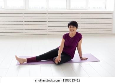 People, yoga, sport and healthcare concept - Relaxed smiling middle-aged woman sitting on exercise mat over white background