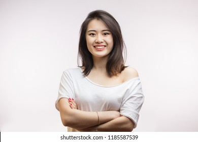 People, youth, beauty and lifestyle concept. Attractive young Asian female student wearing home clothing laughing happily at camera, having rest at home after lectures at college