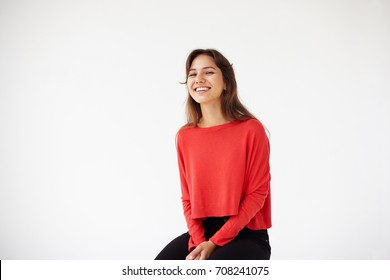 People, youth, joy, fun, leisure and happiness concept. Picture of carefree happy young Hispanic woman in casual red top relaxing in studio, sitting on chair, looking and grinning broadly at camera.