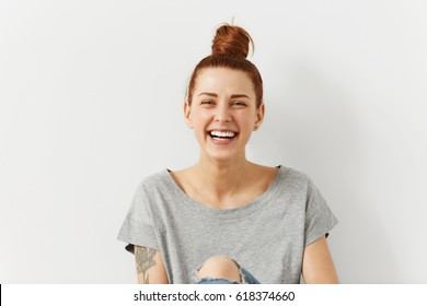 People, youth, leisure and lifestyle concept. Fashionable tattooed young Caucasian young female student wearing stylish clothing laughing happily, having rest at home after lectures at college
