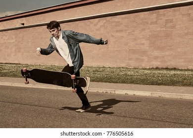 People, youth, urban lifestyle, extreme sports and activity concept. Outdoor action shot of stylish young male in sneakers performing tricks using long board, casting shadow of pavement. Warm filter