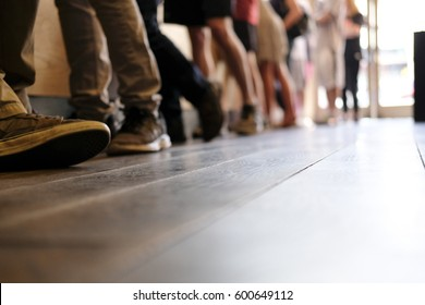 Peoples feet as they wait in line
