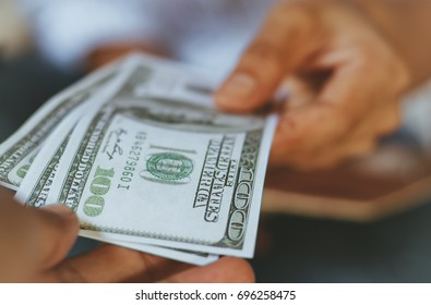 people's hand with many US dollar banknotes giving to someone