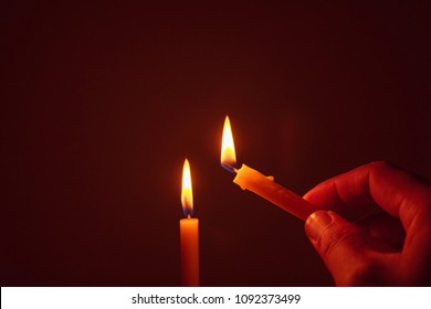 People's hands are lit by candles in the dark. Design for the background, hand with candle, lighting candles.