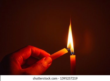 People's hands are lit by candles in the dark. Design for the background, hand with candle, lighting candles, Burning candle on black background, Candle in hand, Candle in the dark.