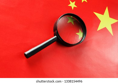 The People's Republic of China a flag is watched through magnifying glass. Spies and observation of People's Republic of China. Monitoring of a condition of China. Concept of danger of theft of milita