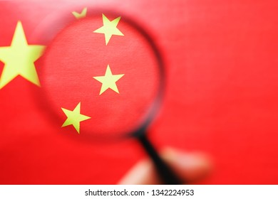 The People's Republic of China a flag is watched through magnifying glass. Spies and observation of People's Republic of China. Monitoring of a condition of China