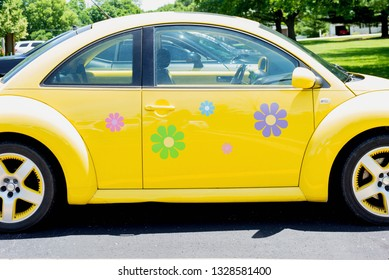 Peoria, IL/USA - 06-13-2018 Bright yellow vw bug with flower decals on a summer day