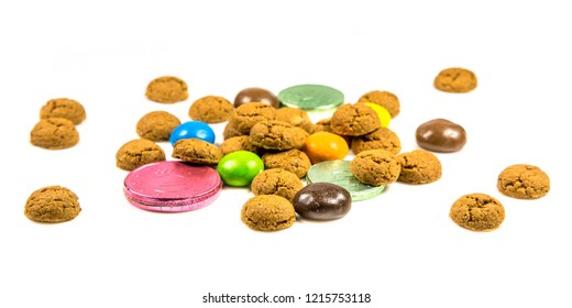 Pepernoten cookies, sweets and chocolate money frontal view on white background for annual Sinterklaas holiday event in the Netherlands on december 5th