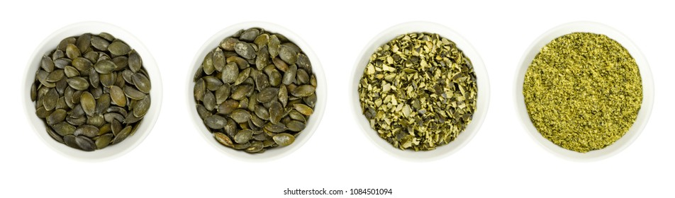 Pepita pumpkin seeds in white porcelain bowls. Raw, roasted, chopped and ground. Flat green summer squash seeds of Cucurbita pepo, genus Cucurbita. Isolated food photo, close up from above over white.