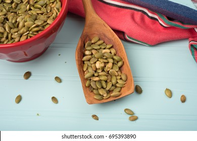 Pepitas Pumpkin Seeds roasted and salted in a red bowl with napkin from above view on rustic teal wood background with space on sides for copy, text or your words. It's  horizontal flat lay display
