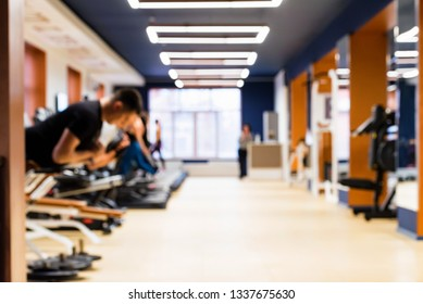 Peple exercise on fitness machines in modern gym interior blurred