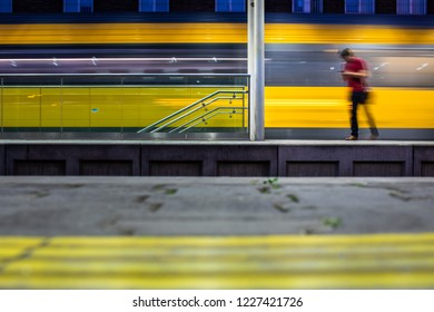 Pepople in a trainstation with motion blurred trains moving fast (color toned image)