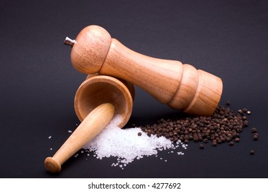 A pepper mill with black peppercorns and a mortar and pestle with sea-salt, against a black background