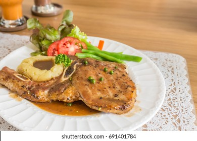 pepper steak made from pork and bone serve with salad and potato baked