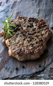 Pepper steak with rosemary, on slate.