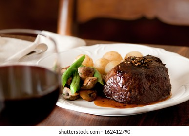 Pepper steak with vegetables and glass of red wine