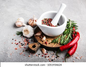 Pepper in white mortar and spices on a gray stone background