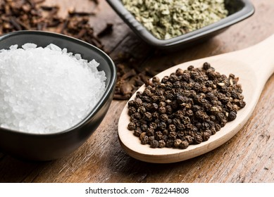 peppercorn in spoon with natural salt and other spices on wooden table.