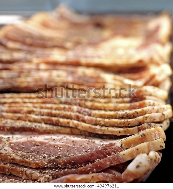 Peppered Bacon slices. Thick cut raw uncooked bacon with pepper seasoning. Smoked country style slice. Front focus, depth of field. Cured sliced bacon stacked on top of each other.