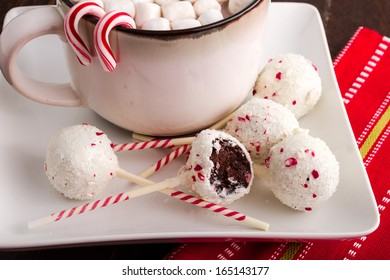 Peppermint brownie cake pops on white plate with mug of hot chocolate and marshmallows and candy canes