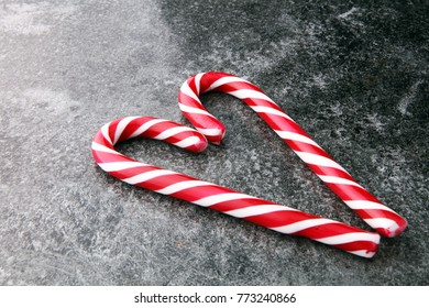 Peppermint Candy Canes in Heart Shape on old wooden background. Christmas.