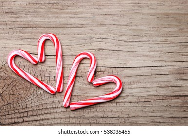 Peppermint Candy Canes in Heart Shapes on wooden background. Christmas