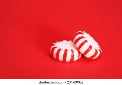Peppermint Candy over Red Christmas background. Macro.