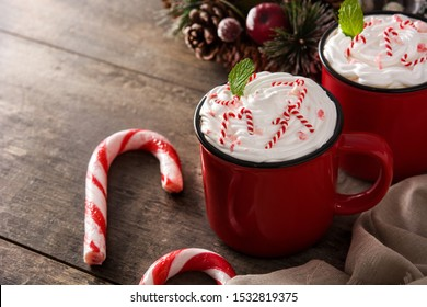 Peppermint coffee mocha decorated with candy canes for Christmas on wooden table.