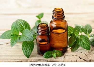 Peppermint essential oil and leaves on the wooden board