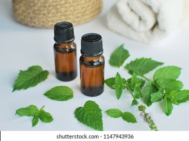 Peppermint essential oil for massage, peppermint leaves, white towels.